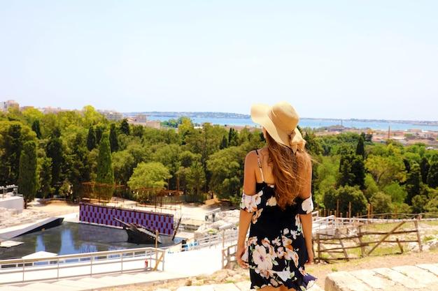 Frau mit hut und kleid in den ständen des griechischen theaters von syrakus, sizilien, italien