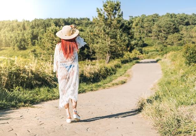 Frau mit hut und weißem kleid zu fuß