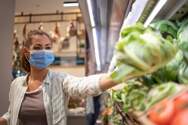 Frau mit hygienemaske und gummihandschuhen und einkaufswagen im lebensmitteleinkauf, der gemüse während des koronavirus kauft und sich für eine pandemiequarantäne vorbereitet