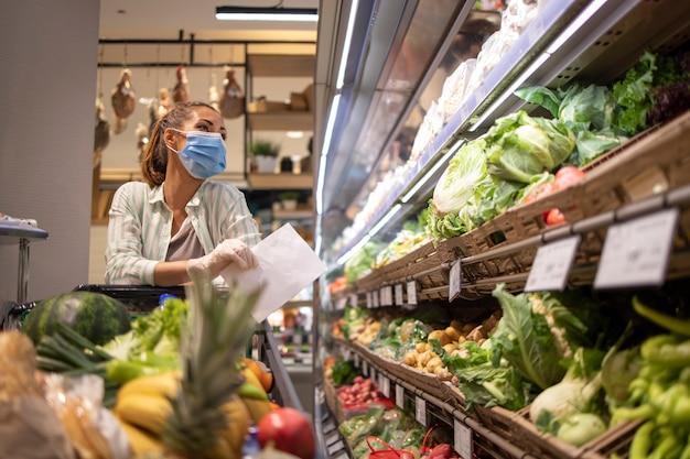 Frau mit hygienemaske und gummihandschuhen und einkaufswagen im lebensmittelgeschäft, das gemüse während des koronavirus kauft und sich für eine pandemiequarantäne vorbereitet