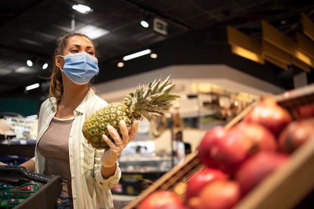 Frau mit hygienemaske und gummihandschuhen und einkaufswagen im lebensmittelgeschäft, das obst während des koronavirus kauft und sich auf eine pandemiequarantäne vorbereitet