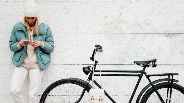 Frau mit ihrem fahrrad, das eine pause vorderansicht nimmt