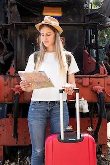 Frau mit ihrem gepäck beim betrachten der karte