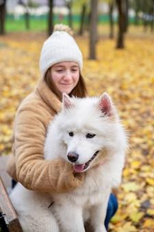 Frau mit ihrem hund im herbst in einem park. frau umarmt es auf der bank und lächelt.