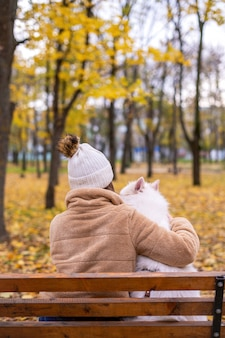 Frau mit ihrem hund im herbst in einem park. frau umarmt es auf der bank.