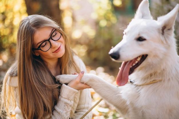 Frau mit ihrem hund im park, der auf decke sitzt