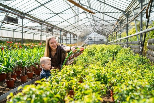 Frau mit ihrem kleinen sohn gießt pflanzen in einem gewächshaus