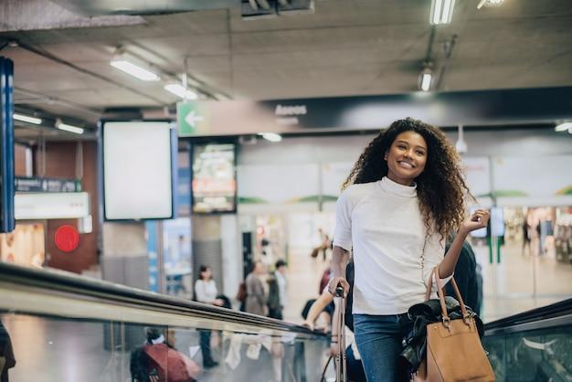 Frau mit ihrem koffer auf rolltreppe am flughafen.