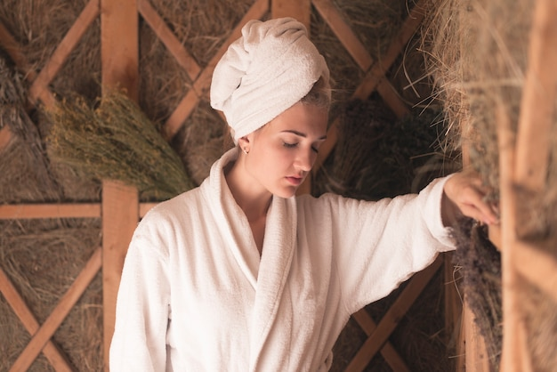 Frau mit ihrem kopf eingewickelt im tuch, das an der sauna sich entspannt