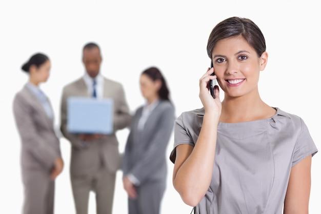 Frau mit ihrem kopf kippte leicht lächelnd am telefon und an den mitarbeitern mit einem laptop