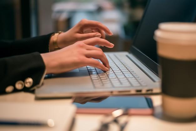 Frau mit ihrem laptop in einem café. seitenansicht der jungen frau, die an einem tisch mit einer tasse kaffee und einem handy sitzt, das das netz auf ihrem laptop-computer surft.