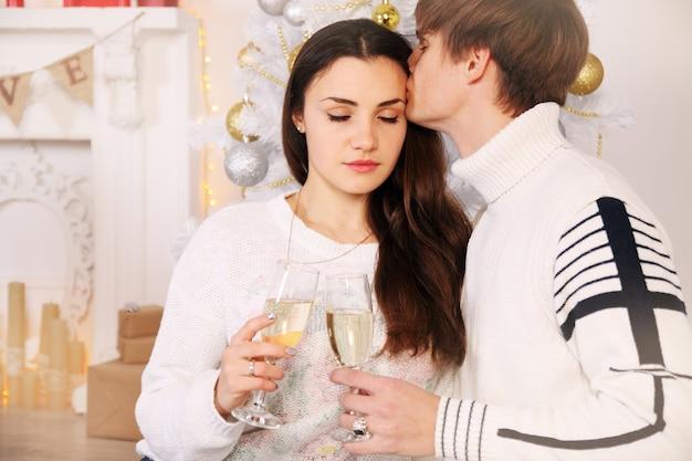 Frau mit ihrem mann am weihnachtsbaum sitzen