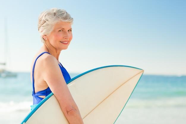 Frau mit ihrem surfbrett am strand
