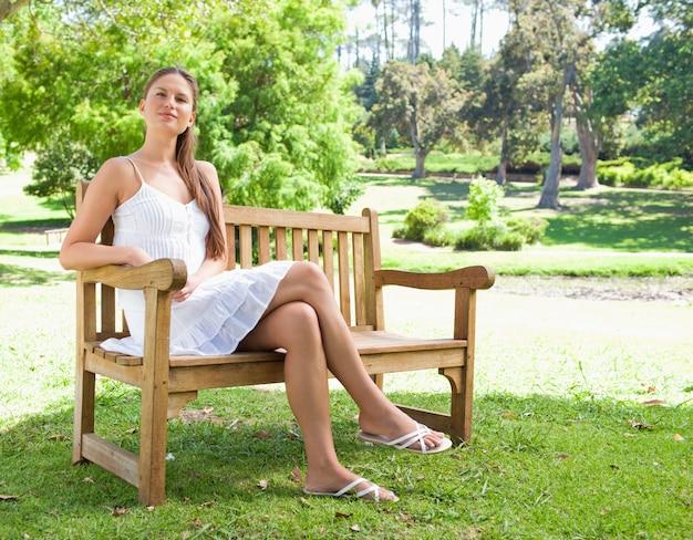 Frau mit ihren beinen kreuzte das sitzen auf einer bank