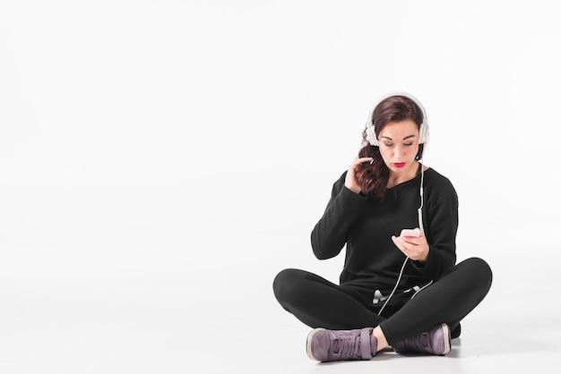 Frau mit ihrer hand in hörender musik des haares auf kopfhörer durch mp3-player