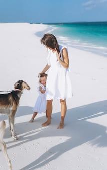 Frau mit ihrer kleinen tochter, die mit hunden am strand durch den ozean spielt