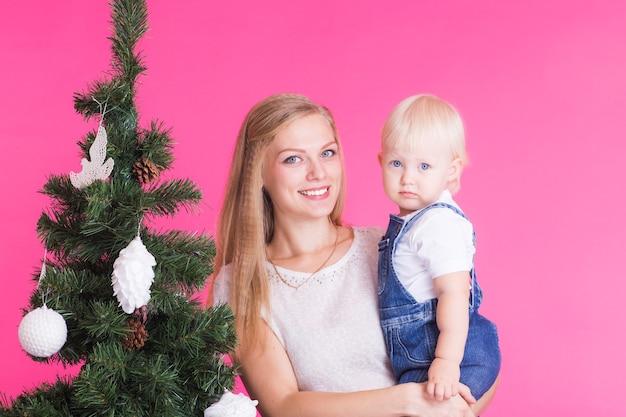 Frau mit ihrer kleinen tochter, die weihnachtsbaum schmückt