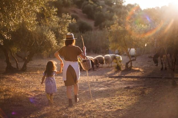 Frau mit ihrer tochter, die schafe auf dem gebiet in herden lebt