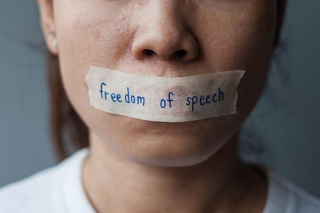 Frau mit in klebeband versiegeltem mund mit botschaft zur redefreiheit., pressefreiheit, menschenrechte, protestdiktatur, demokratie, freiheit, gleichheit und brüderlichkeitskonzepte