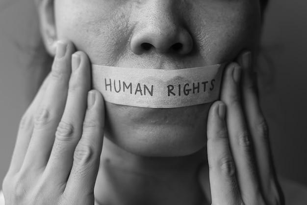 Frau mit in klebeband versiegeltem mund mit menschenrechtsbotschaft. meinungsfreiheit, pressefreiheit, protestdiktatur, demokratie, freiheit, gleichheit und brüderlichkeitskonzepte