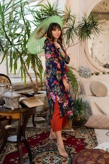 Frau mit japanischem regenschirm, der in boho-innenraum mit tropischen pflanzen und stilvollen möbeln knallt.