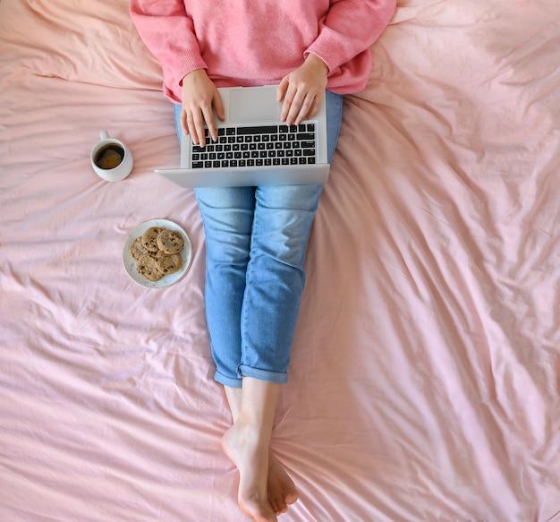 Frau mit jeans sitzt auf dem rosa bett mit tasse kaffee und arbeitet an ihrem laptop. usa