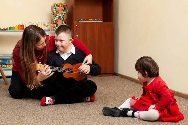 Frau mit jungen mit down-syndrom und gitarre