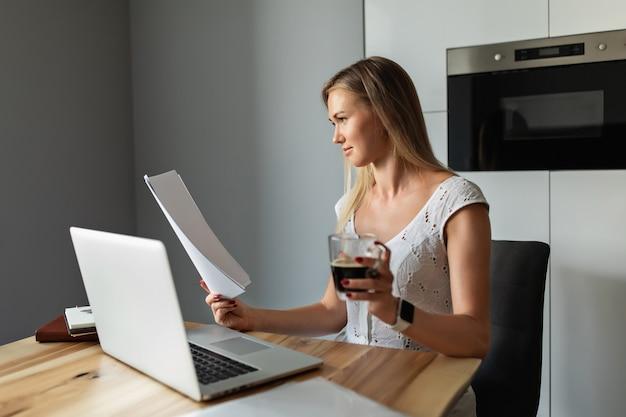 Frau mit kaffee, der am laptop im hauptbüro arbeitet