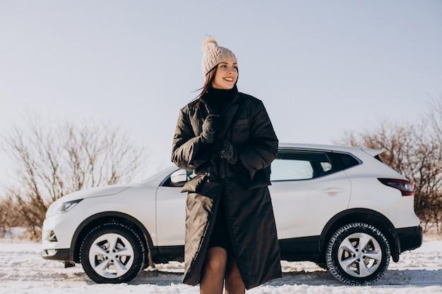 Frau mit kaffee, der durch auto in einem winterfeld steht