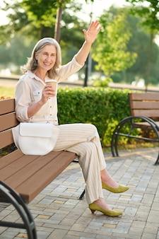 Frau mit kaffee, der zur begrüßung die hand hebt