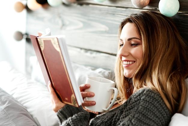 Frau mit kaffeelesebuch im schlafzimmer