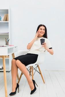 Frau mit kaffeetasse telefonisch im büro sprechen