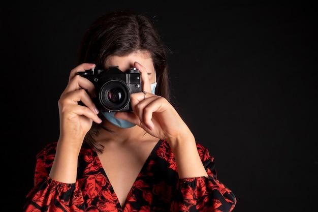 Frau mit kamera und maske beim fotografieren