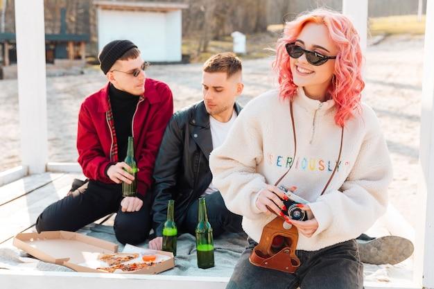 Frau mit kamera und paar mann auf picknick