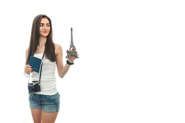 Frau mit kamera und pässen, die eiffelturm halten