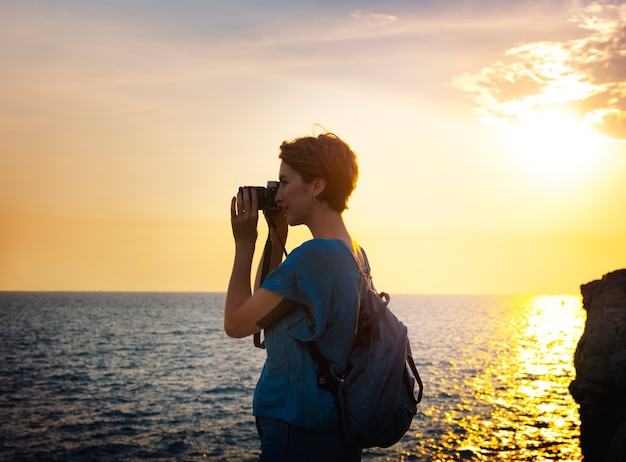 Frau mit kameraschießen am strand