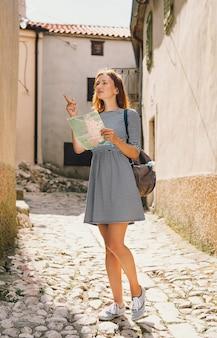 Frau mit karte zeigt seite auf dem hintergrund der alten europäischen straßen insel krk kroatien