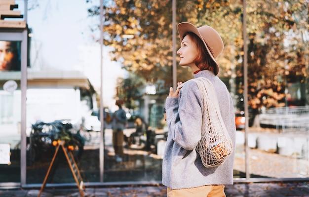 Frau mit kauf in wiederverwendbarer netztasche aus baumwolle und glasbecher auf der schaufensterfront des zero-waste-ladens