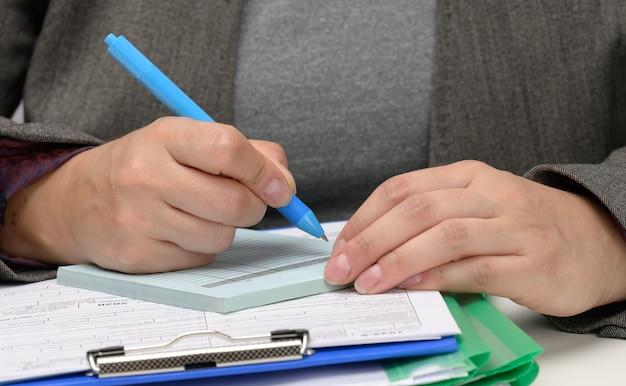Frau mit kaukasischem aussehen sitzt in grauer kleidung an einem weißen tisch und unterschreibt dokumente mit einem metallstift. geschäftsmann bei der arbeit, unterschrift auf vertrag und rechnung, nahaufnahme