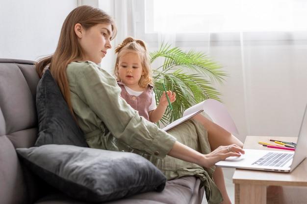Frau mit kind, das am laptop arbeitet