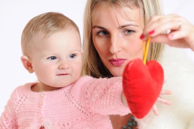 Frau mit kind, das mit interesse spielzeug in form des roten herzens betrachtet. baby mit grauen augen in rosa kleidern