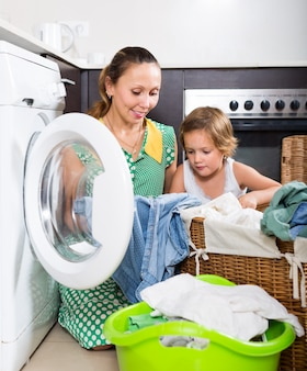Frau mit kind nahe waschmaschine
