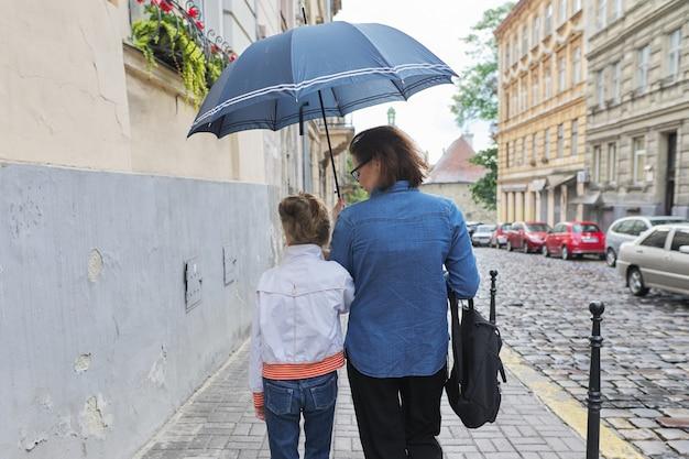 Frau mit kindermädchen, das unter einem regenschirm in straße geht