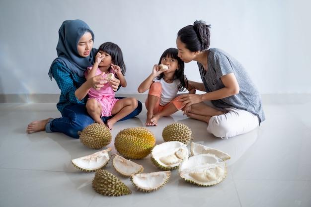Frau mit kindern, die durianfrucht essen