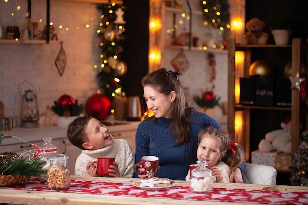 Frau mit kindern in einer weihnachtlich dekorierten küche