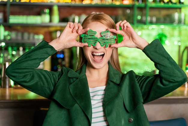 Frau mit kleeblattgläsern, die st feiern. patricks tag an der bar