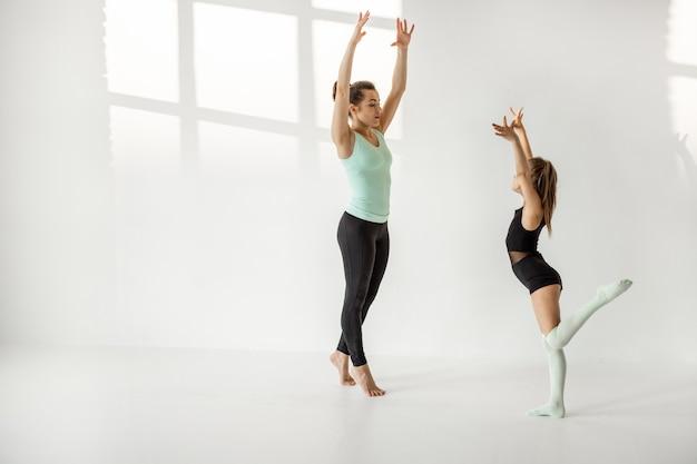 Frau mit kleinem mädchen beim rhythmischen gymnastiktraining