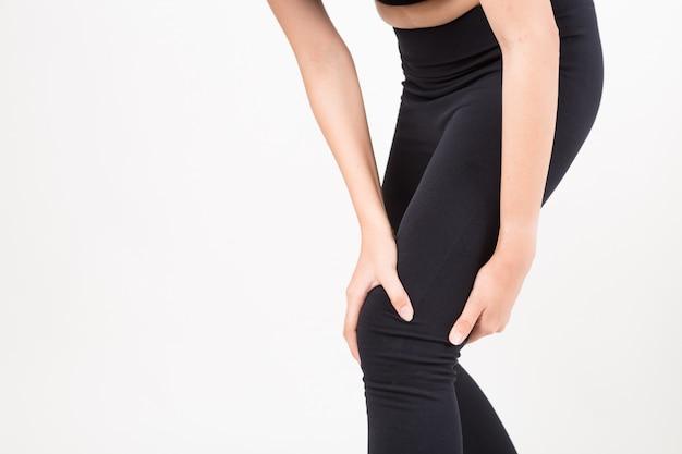 Frau mit knieschmerz. atelieraufnahme auf weißem hintergrund. fitness- und gesundheitskonzept