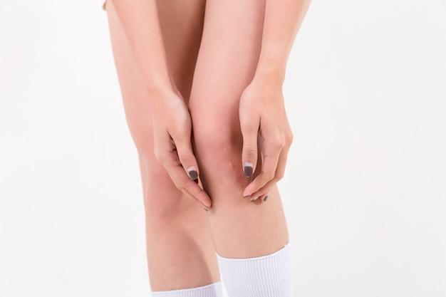 Frau mit knieschmerzen isoliert auf weißem hintergrund. studiobeleuchtung. konzept für gesund und medizinisch