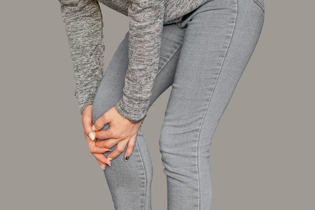 Frau mit knieschmerzen. schmerzen im knie bei einer frau